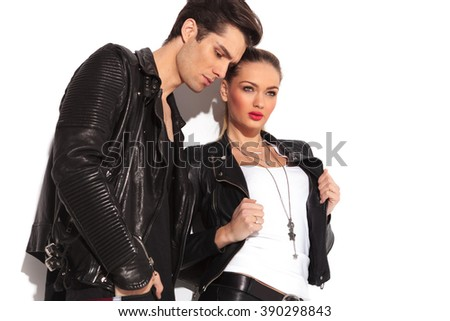 side view of a fashion couple in leather jackets standing in studio and look away from the camera, man is looking down, woman is pulling her jacket's collar - stock photo