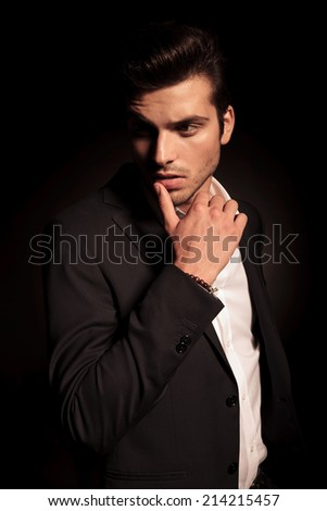 side view of a fashion man in a provocative pose with finger on his lip , looking away from the camera - stock photo