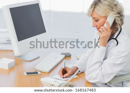 Side view of a female doctor using phone while writing notes at medical office - stock photo