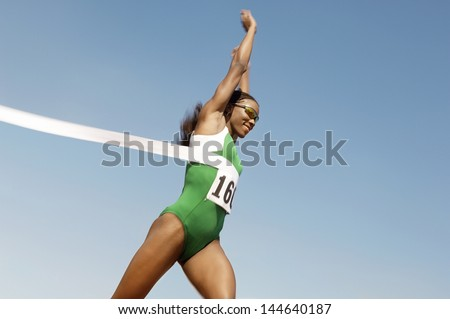 Side view of a female runner winning race against the blue sky - stock photo