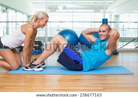 Side view of a female trainer assisting young man with abdominal crunches at fitness studio - stock photo