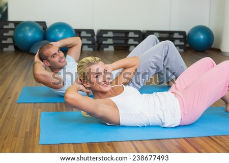 Side view of a fit couple doing abdominal crunches at the gym - stock photo