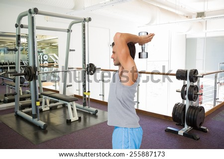 Side view of a fit man exercising with dumbbell against empty weights room with bench press - stock photo