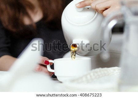 side view of a girls pouring tea - stock photo
