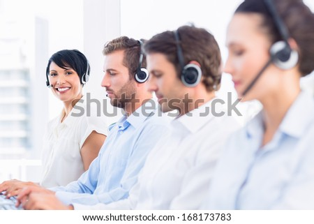 Side view of a group of business colleagues with headsets in a row at office - stock photo