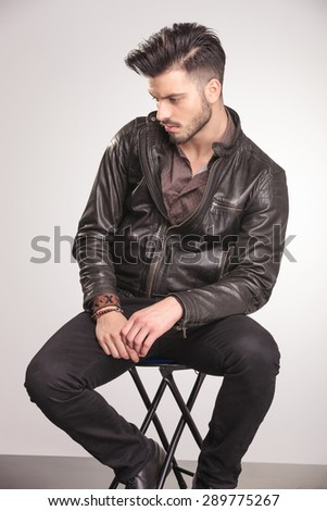 Side view of a handsome young fashion man sitting on a chair while looking down. - stock photo