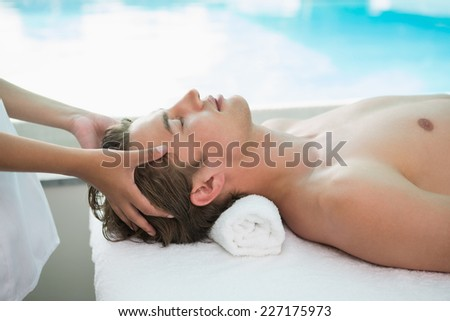 Side view of a handsome young man receiving head massage at spa center - stock photo