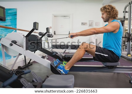 Side view of a handsome young man using resistance band in gym - stock photo