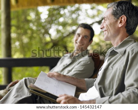 Side view of a happy man with book sitting on terrace with blurred male friend in background - stock photo