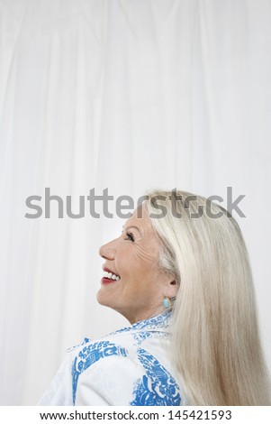 Side view of a happy senior woman looking up against white background - stock photo