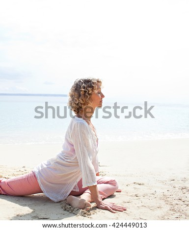 Side view of a healthy senior woman in yoga position, meditating on the shore of a transparent sea in a coastal beach destination, sunny outdoors. Sporty travel lifestyle, spacious nature exterior. - stock photo