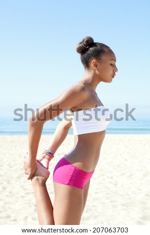 Side view of a healthy sporty young african american woman stretching her legs, exercising and training against a blue sea and sky during a sunny day on a sandy beach. Sport lifestyle outdoors. - stock photo