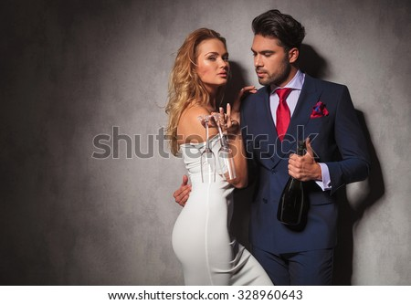 side view of a hot couple holding a bottle of champagne , man is looking at his woman while she is holding two glasses - stock photo