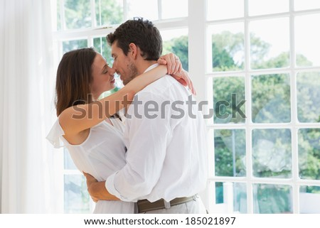 Side view of a loving young couple about to kiss at home - stock photo