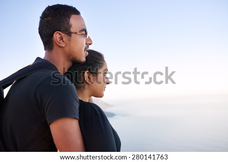 Side view of a loving young Indian couple standing closely together and looking into the distance - stock photo