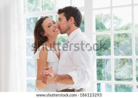 Side view of a loving young man kissing woman at home - stock photo