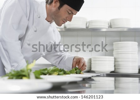 Side view of a male chef preparing salad in kitchen - stock photo