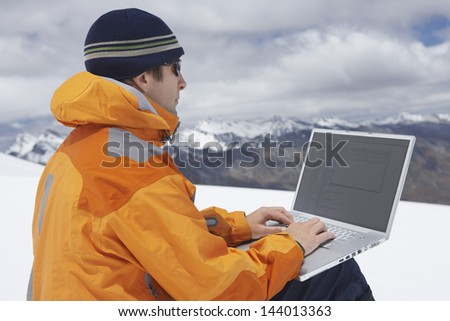 Side view of a male hiker using laptop on snowy mountain landscape - stock photo