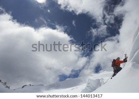 Side view of a male mountain climber going up snowy slope with axes against clouds - stock photo