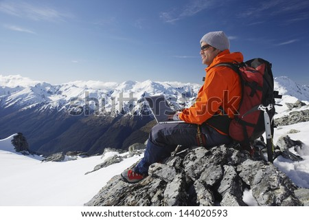 Side view of a male mountain climber using laptop on mountain peak - stock photo