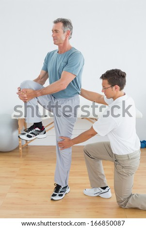 Side view of a male therapist helping man with stretching exercises in the gym at hospital - stock photo