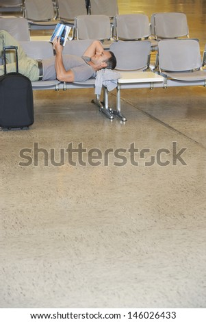 Side view of a male traveler lying on chairs and reading book in airport lobby - stock photo