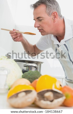 Side view of a man preparing food with vegetables in the foreground at kitchen - stock photo