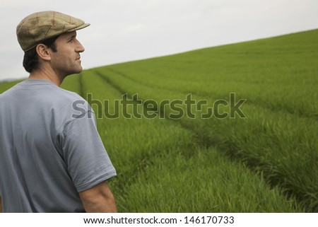 Side view of a man standing in tilt field - stock photo