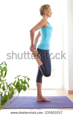 Side view of a mature healthy sporty woman using a yoga mat to exercise and stretch her body in a light and airy interior. Fit professional woman exercising and stretching her body, indoors. - stock photo