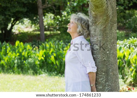 Side view of a mature woman leaning against tree trunk in the park - stock photo