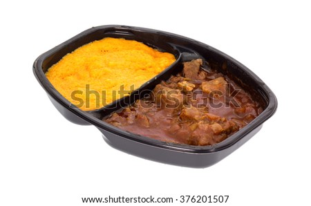 Side view of a microwaved braised beef in gravy with sweet potatoes TV dinner in a black tray isolated on a white background. - stock photo