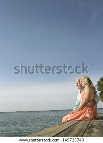 Side view of a middle aged couple sitting on edge of pier - stock photo