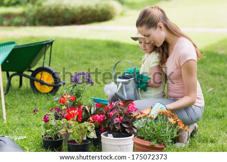 Side view of a mother and daughter engaged in gardening - stock photo