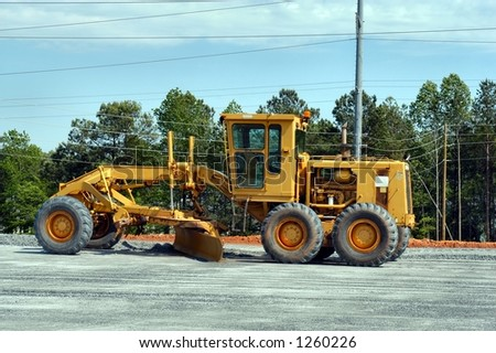 Side view of a motor grader at rest - stock photo