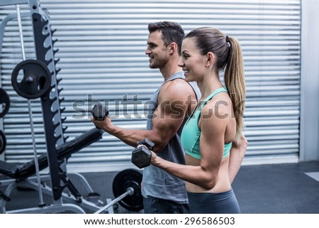 Side view of a muscular couple lifting dumbbells - stock photo