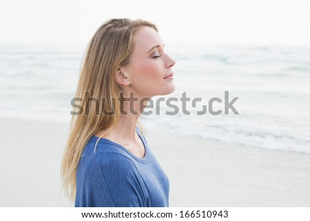 Side view of a peaceful casual young woman with eyes closed at the beach - stock photo