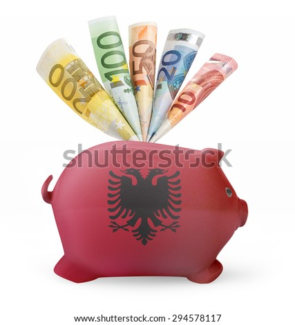 Side view of a piggy bank with the flag design of Albania and various european banknotes.(series) - stock photo