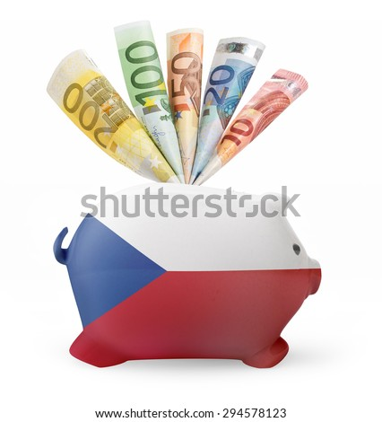 Side view of a piggy bank with the flag design of Czech Republic and various european banknotes.(series) - stock photo