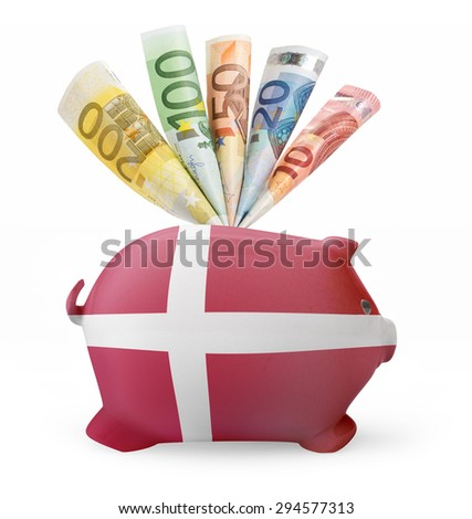 Side view of a piggy bank with the flag design of Denmark and various european banknotes.(series) - stock photo