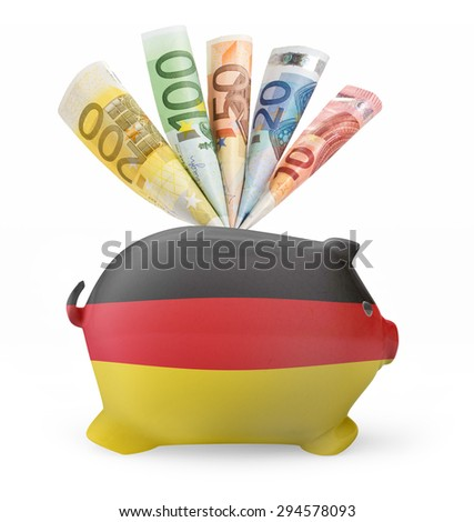 Side view of a piggy bank with the flag design of Germany and various european banknotes.(series) - stock photo