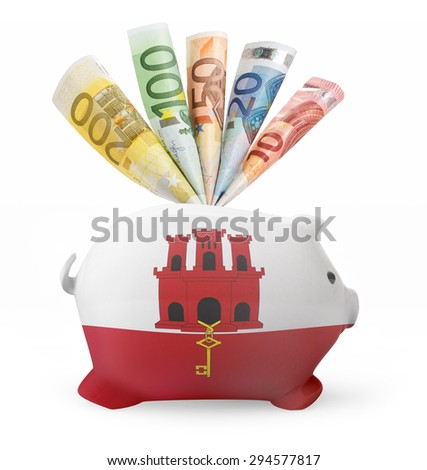 Side view of a piggy bank with the flag design of Gibraltar and various european banknotes.(series) - stock photo