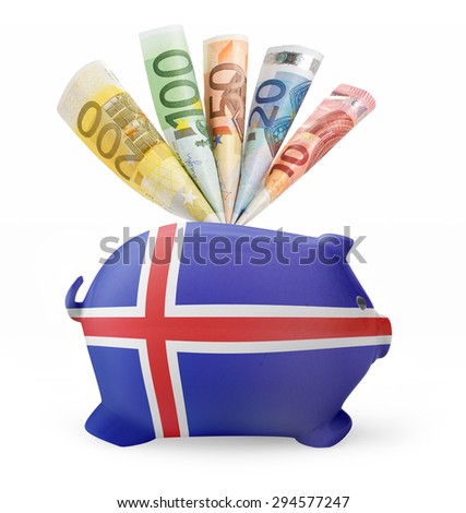 Side view of a piggy bank with the flag design of Iceland and various european banknotes.(series) - stock photo