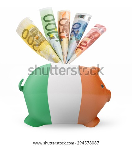 Side view of a piggy bank with the flag design of Ireland and various european banknotes.(series) - stock photo