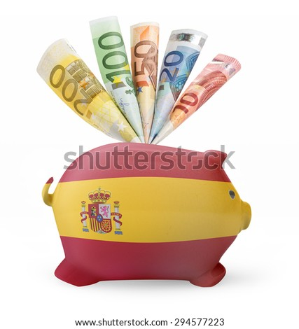 Side view of a piggy bank with the flag design of Spain and various european banknotes.(series) - stock photo