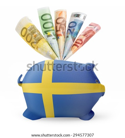 Side view of a piggy bank with the flag design of Sweden and various european banknotes.(series) - stock photo