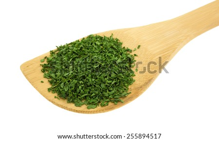 Side view of a portion of dried chopped parsley flakes on a wood spoon atop a white background. - stock photo