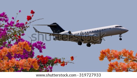 Side view of a private jet flying - stock photo