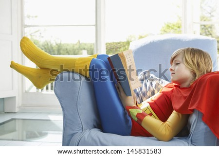 Side view of a relaxed young boy in superhero costume reading book on armchair - stock photo