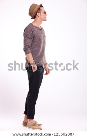 side view of a relaxed young casual man holding a hand in his pocket and looking away from the camera, on a light background - stock photo