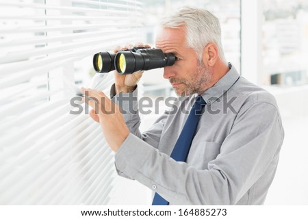 Side view of a serious mature businessman peeking with binoculars through blinds in the office - stock photo